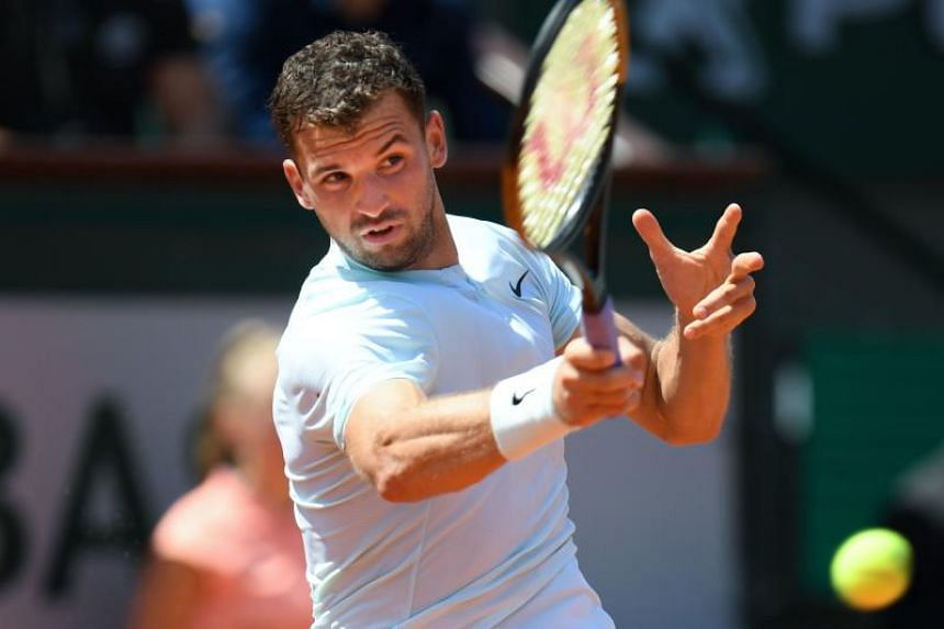 Grigor Dimitrov returning a shot to Mohamed Safwat during their men's singles first round match at the French Open on May 27, 2018.