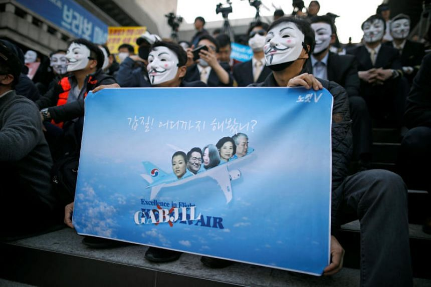 People holding a banner showing the relatives of Korean Air chairman Cho Yang Ho during a protest on May 4, 2018.
