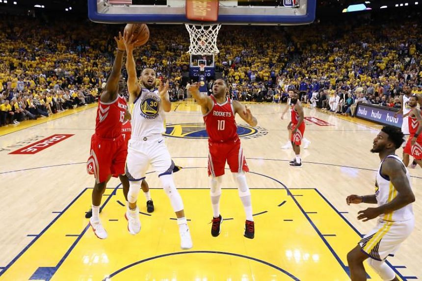 Golden State Warriors guard Stephen Curry (#30) going up for a layup against Houston Rockets centre Clint Capela (#15) and guard Eric Gordon (#10) during their NBA match on May 27, 2018.