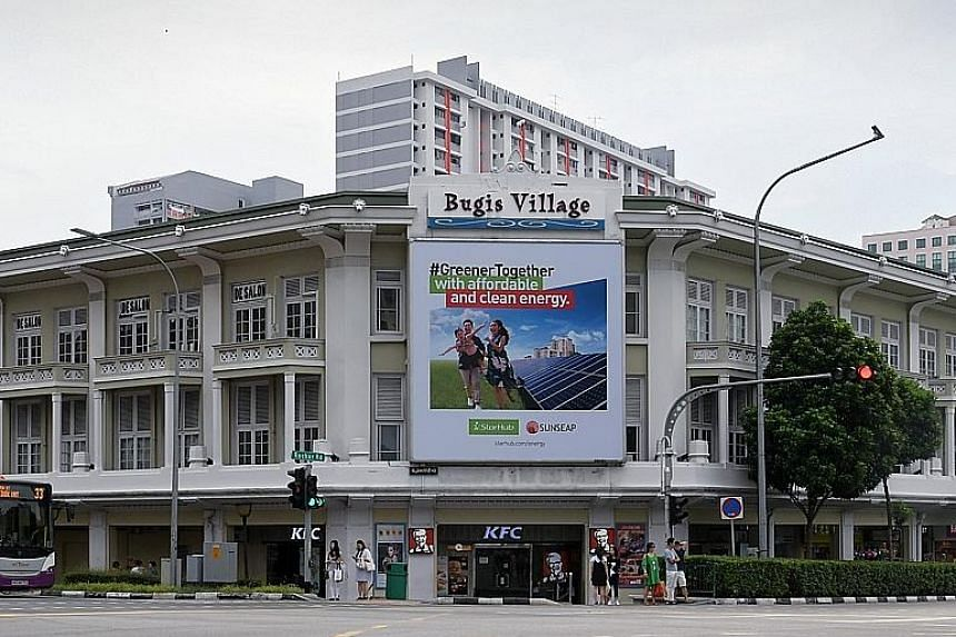 Tenants of the shophouses include retail outlets and eateries like the Cat Cafe (right). Bugis Village comprises a cluster of 34 three-storey shophouses built before World War II. They do not have conservation status and are designated for commercial