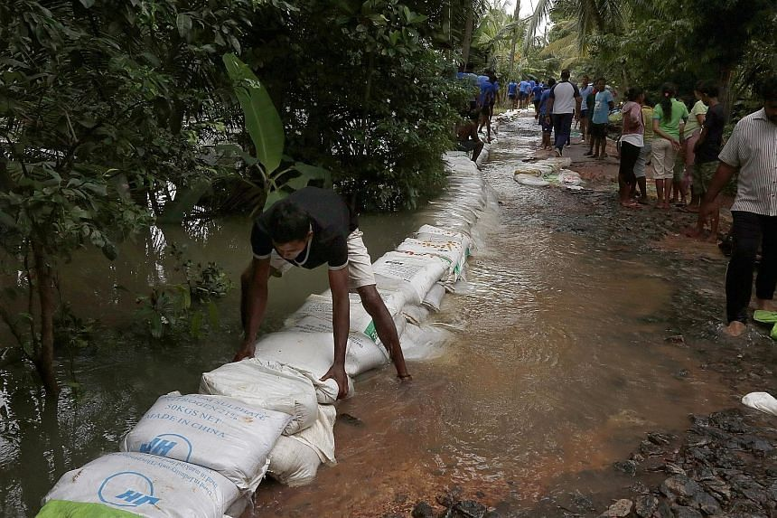 Sri Lankan volunteers placing sandbags to protect a road from floodwaters at Ja Ela, near the capital Colombo, over the weekend. Monsoon rains have started in Sri Lanka, bringing floods to many parts of the island. According to the government's disas