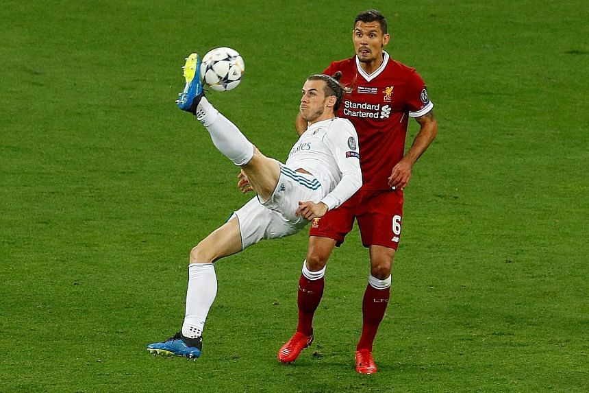 Real Madrid's Cristiano Ronaldo (top) indicating that he now has five Champions League trophies, with Gareth Bale's spectacular bicycle-kick goal (above) helping to secure the latest.