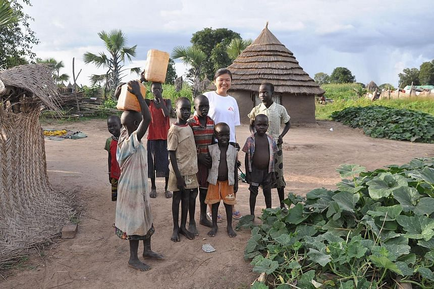 "Miss Lim Suet Fong with a group of village children in Pibor, South Sudan, when she was a field worker with Doctors Without Borders. The civil engineer says she has ""gained a lot more than what I have given"" during her two missions - in South Sudan a"
