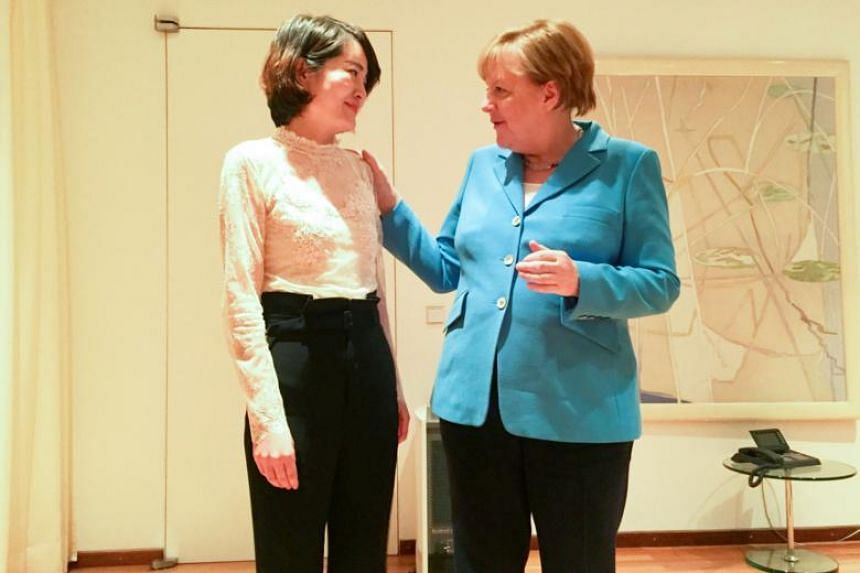 German Chancellor Angela Merkel (right) speaking with Li Wenzu in Beijing, China. Dr Merkel did not mention the meeting with the two women during her two-day visit to China.