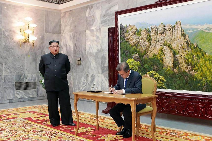 South Korea's President Moon Jae In (right) signing a guestbook as North Korea's leader Kim Jong Un looks on during their second summit on May 26, 2018.