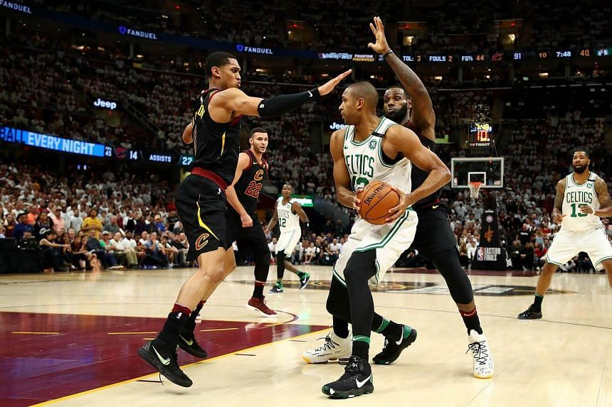 Al Horford of the Boston Celtics handles the ball against Jordan Clarkson and LeBron James of the Cleveland Cavaliers at Quicken Loans Arenain in Ohio, on May 25, 2018.