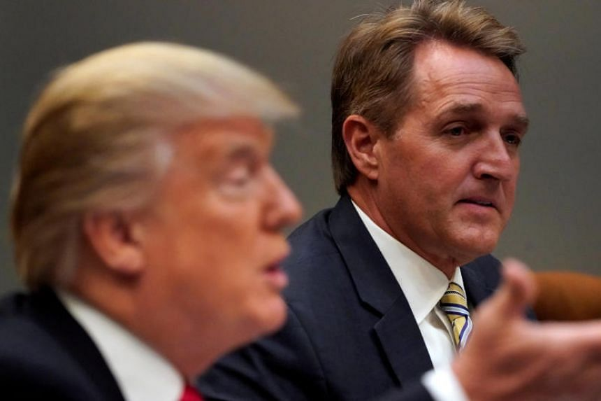 US President Donald Trump, flanked by US Senator Jeff Flake, at the White House in Washington, on Dec 5, 2017.