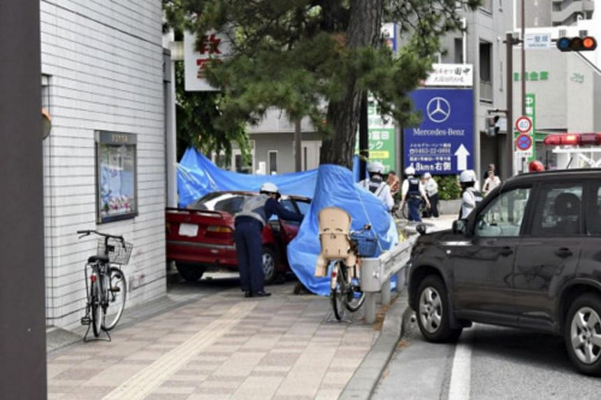 A police officer observing the site of an accident, where a 90-year-old driver mounted the kerb at a busy crossroads, in Chigasaki city, Kanagawa prefecture, on May 28, 2018.