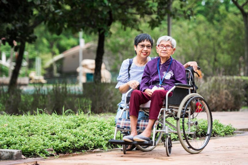 """Madam Sarah Liew and her 85-year-old mother, who has dementia. Madam Liew said that the family had """"totally forgotten"""" that her mother was covered by ElderShield until they were reminded by staff at her mother's care centre."""