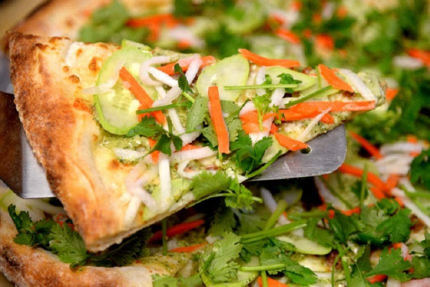 Slice`s banh mi pizza pairs cheese and lemongrass-infused pork sausage with a piquant, cliantro-based sauce, cucumber, pickled carrots and daikon radish.
