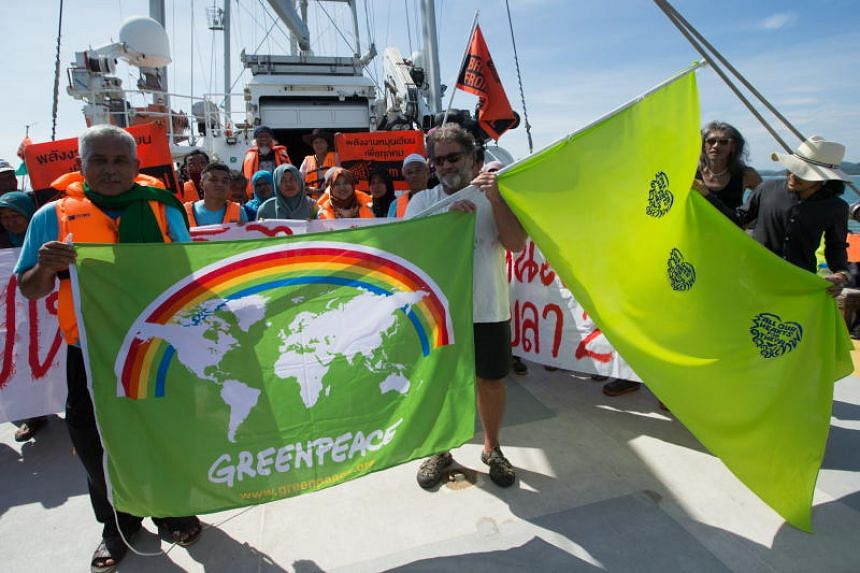 Community representatives hold flags aboard Rainbow Warrior during a protest against a coal-fired project in the Gulf of Thailand on May 21, 2018.