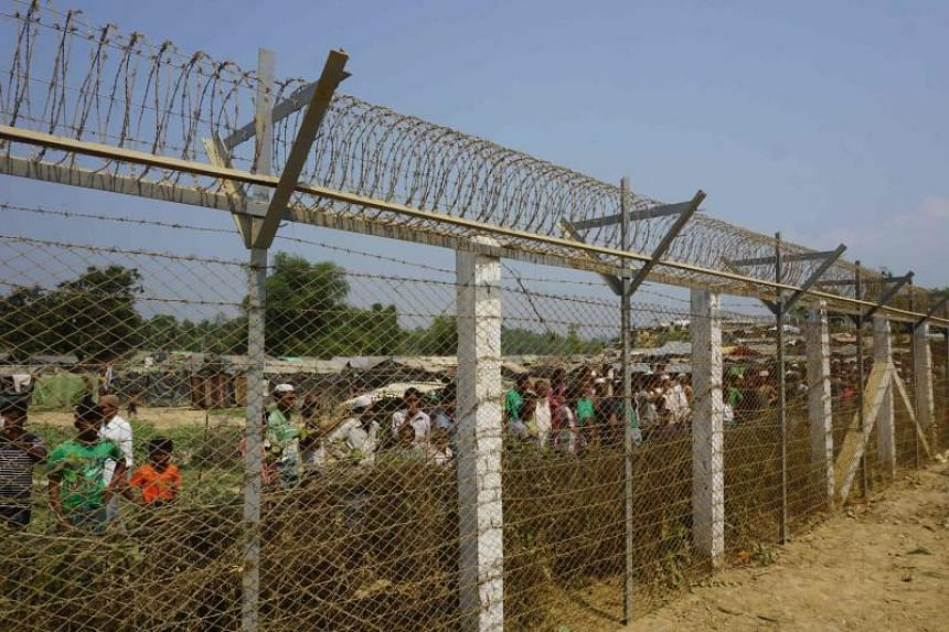 Rohingya Muslims gather behind Myanmar's border lined with barbed wire fences in Maungdaw district, located in Rakhine State bounded by Bangladesh, on March 17, 2018.