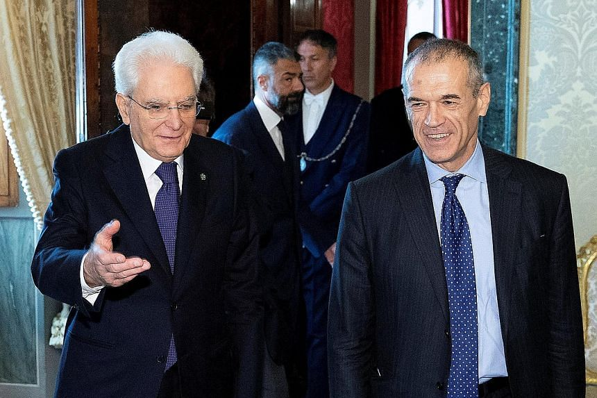 Italian President Sergio Mattarella (left) welcoming caretaker prime minister Carlo Cottarelli to Quirinal Palace in Rome for talks. Mr Cottarelli said elections could be held after August if his government loses a parliamentary vote of confidence, o