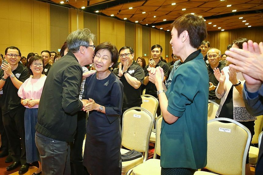 Right: Former manpower minister Lim Swee Say holding a miniature figure of himself that was presented to him. Far right: Mr Lim kisses his wife after giving a speech, as current Manpower Minister Josephine Teo looks on.