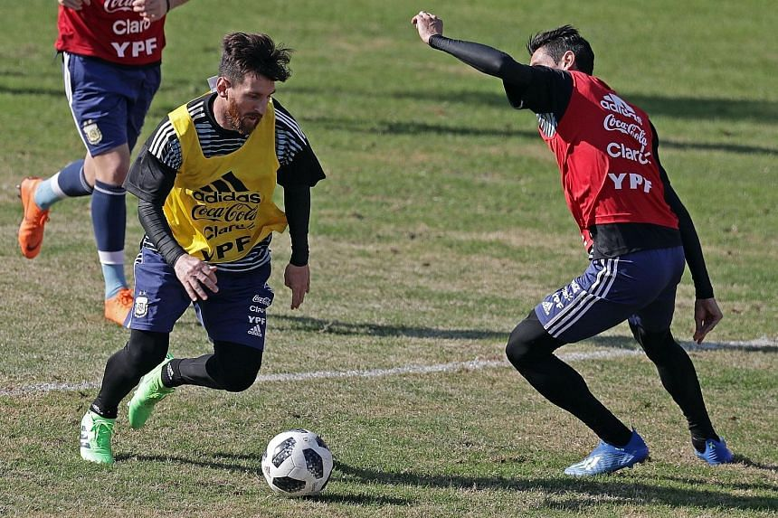 Argentina's Lionel Messi (left) tries to get past team-mate Angel di Maria during training in Buenos Aires on Sunday before their friendly match against Haiti today. Besides an Olympic gold in Beijing 2008, Messi has never won a major tournament with