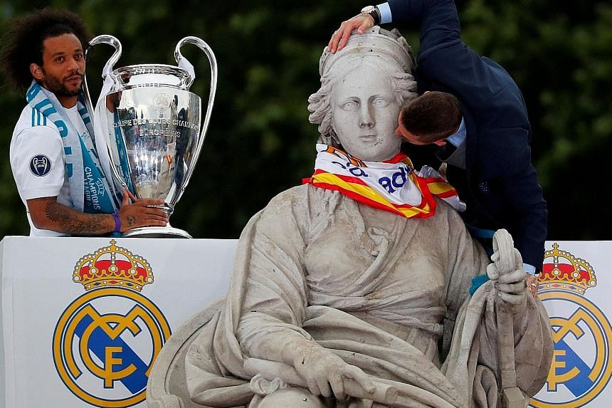Real Madrid captain Sergio Ramos giving the Greek goddess Cybele, the ancient Phrygian Mother of the Gods, a peck on her cheek while team-mate Marcelo keeps watch over the Champions League trophy during the team's victory parade past the iconic Plaza