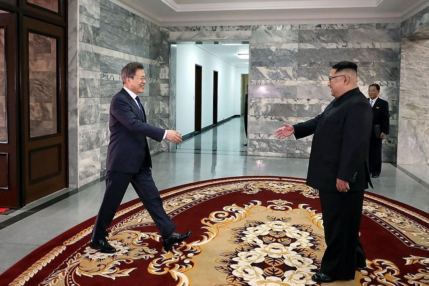 South Korean President Moon Jae In (far left) greeting North Korean leader Kim Jong Un before their second summit at the truce village of Panmunjom, on Saturday, in a handout photo released by South Korea's presidential Blue House yesterday. The US-S