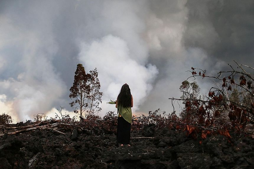 A traditional hula practitioner standing on a recent lava flow from a Kilauea volcano fissure on Hawaii's Big Island on Sunday, when offerings were left in a ceremony for Madame Pele, the Hawaiian goddess of volcanoes and fire. Hula is a Hawaiian dan