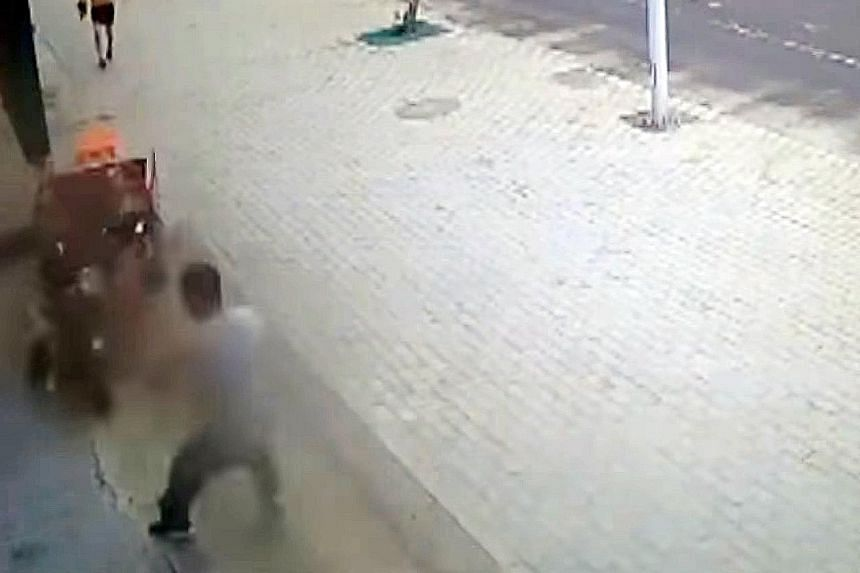 Scenes from the video showing the heroic actions of a shopkeeper in China who saves a girl dangling off the side of a runaway three-wheeler heading towards a wall.