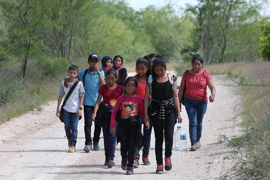 File photo showing people who had illegally crossed the Mexico-US border walking up a dirt road near McAllen, Texas, on May 9, 2018.