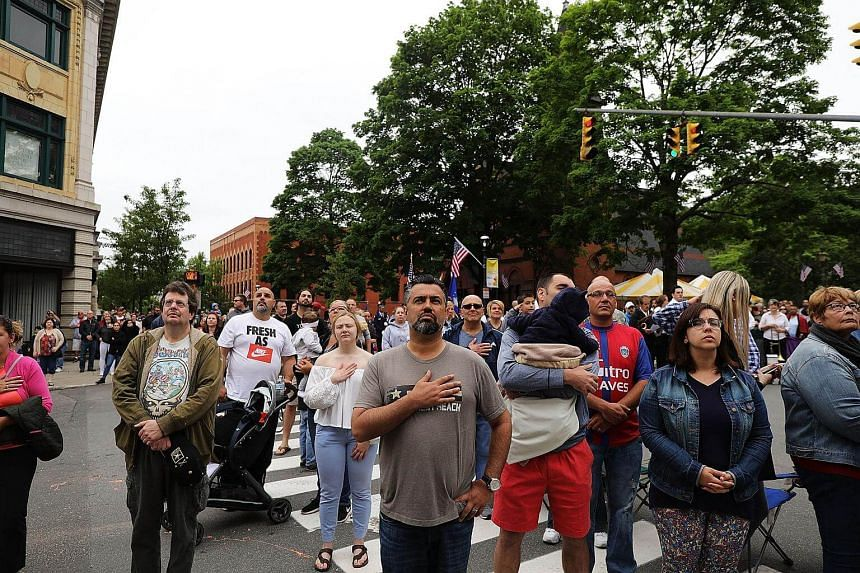 People pause for the playing of the national anthem during the annual Memorial Day Parade in Naugatuck, Connecticut, on May 28, 2018.