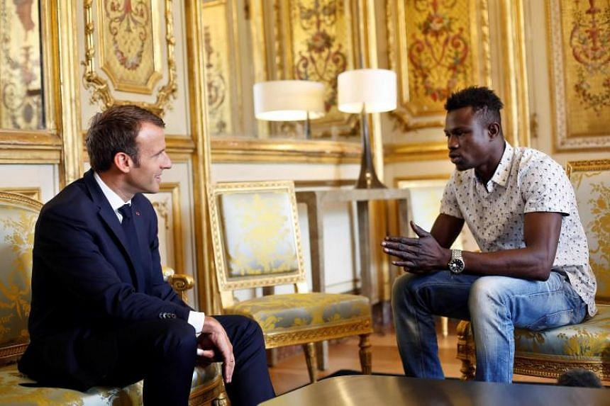 French President Emmanuel Macron (left) speaks with Mamoudou Gassama, 22, from Mali, at the presidential Elysee Palace in Paris, on May, 28, 2018.