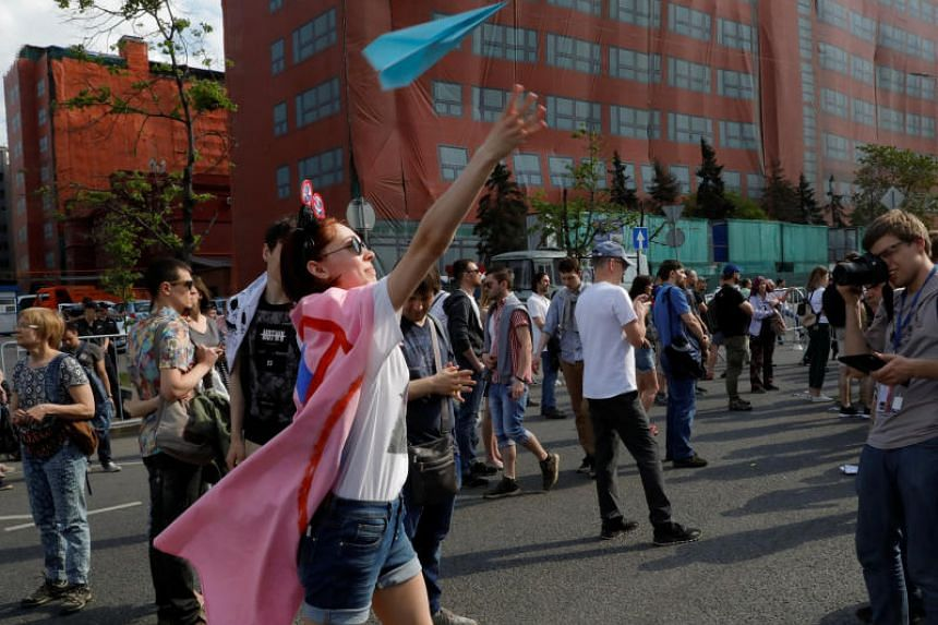 A youth releases a paper plane, symbol of the Telegram messenger, during a rally in protest against court decision to block the messenger because it violated Russian regulations, in Moscow, Russia, on May 13, 2018.