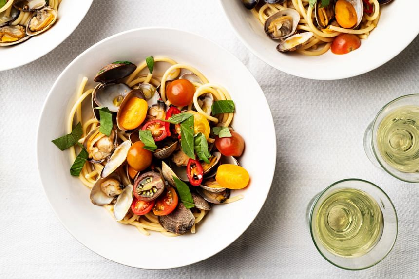 Halved cherry tomatoes and fresh basil finish off a summery take on spaghetti and clams.