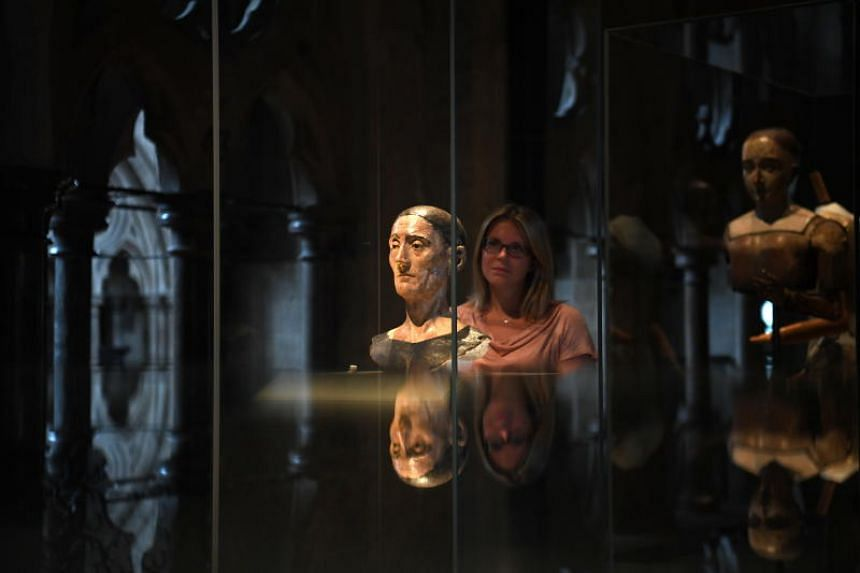 A gallery assistant poses with death mask of King Henry VII during the press preview of The Queen's Diamond Jubilee Gallery at Westminster Abbey in London on May 29, 2018.