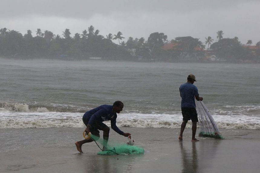 Fishermen prepare to cast their nets during a sudden downpour at Fort Kochi beach in the southern state of Kerala, India, on May 28, 2018.