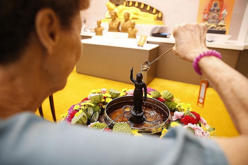 Devotees mark Vesak Day in different ways around the island. From left: At Thekchen Choling, Singapore's only 24-hour Tibetan Buddhist temple, a devotee spins the Giant Mani Wheel for purification while other devotees practise the offering of robes o
