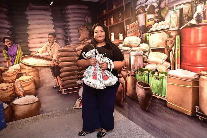 Nida Nur Adawiyah with bags of rice that will be delivered to needy households as part of the Paddy Project.