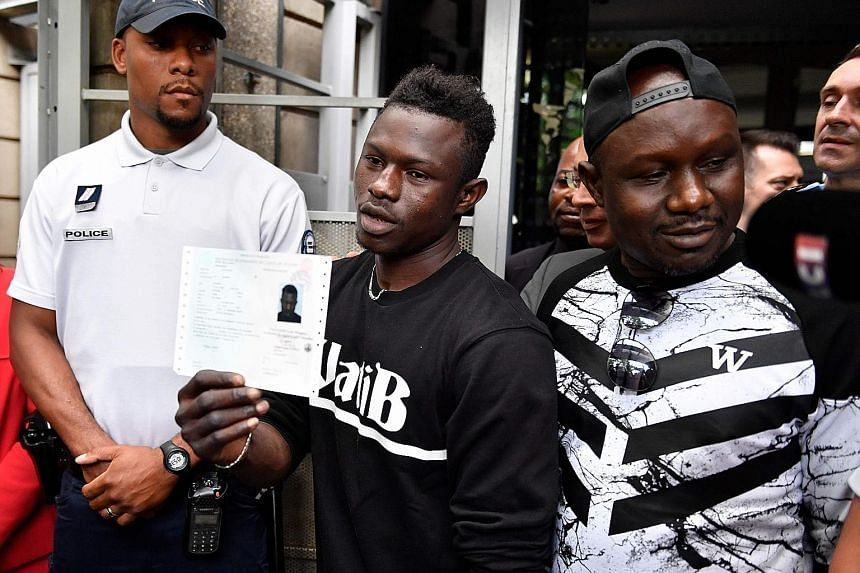 Malian migrant Mamoudou Gassama holding his temporary French residence permit yesterday. With him is his older brother.