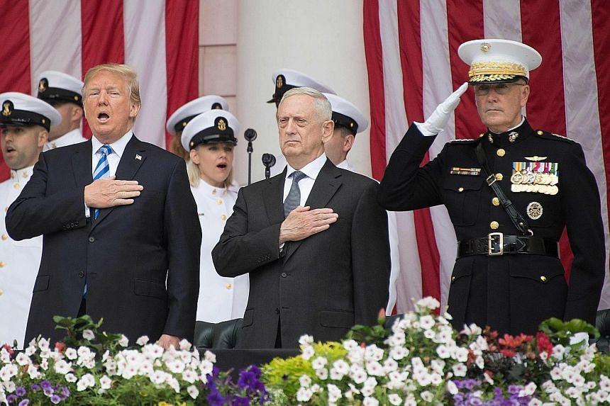From left: US President Donald Trump, with US Secretary of Defence James Mattis and Chairman of the Joint Chiefs of Staff General Joseph Dunford, singing the national anthem during a Memorial Day ceremony at Arlington National Cemetery in Arlington,