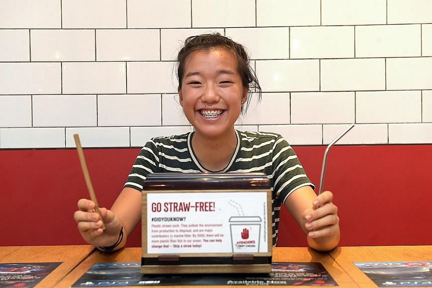 Student Ang Zyn Yee with a wooden straw and a metal straw which she carries with her at all times, and the sticker that she designed for fast-food chain 4Fingers Crispy Chicken, which encourages diners to go straw-free.