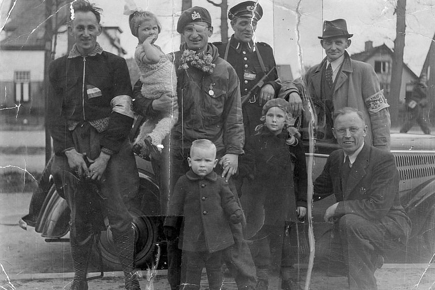 Mr Leo Major (second from left), with officials and children the morning after the liberation of Zwolle, the Netherlands. Mr Major lost sight in his left eye after a German threw a grenade at him.