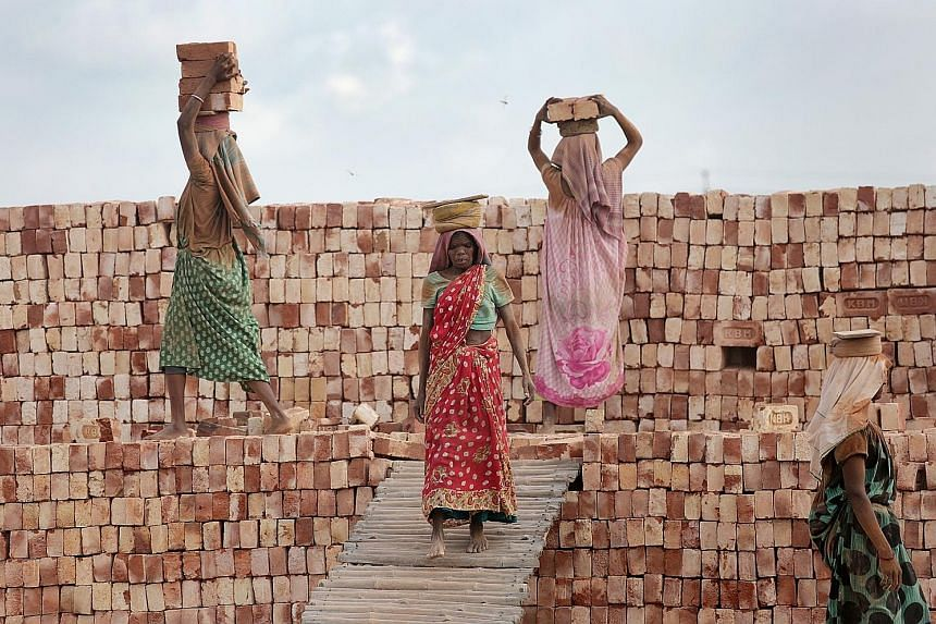 Indian labourers working in a brick field during a hot afternoon in Nagda village, 55km north of Kolkata in eastern India, yesterday. The summer, or pre-monsoon season, occurs from March to July in eastern India, with highest daytime temperatures ran