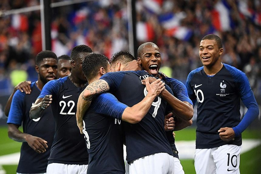 France forward Olivier Giroud (No. 9) is embraced by team-mates after scoring the first goal in the 2-0 win against the Republic of Ireland in a friendly at the Stade de France on Monday. Les Bleus will take on Australia in their World Cup opener in