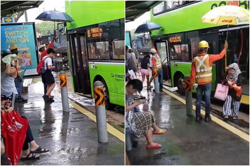 The foreign workers were armed with an umbrella each at a bus stop in Sengkang at around 10am on May 28, 2018. They had stationed themselves there to shelter commuters boarding buses due to the heavy rain.