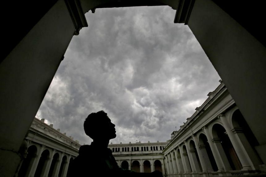 An Indian man looks up as dense cloud coveres the city sky before rain in Kolkata, Eastern India, on May 18, 2018.