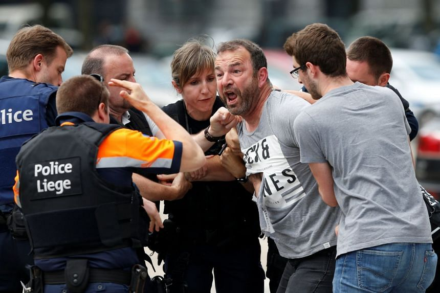 A man is taken away by police officers after crossing the security zone on the scene of a high school shooting in Liege, Belgium, on May 29, 2018.