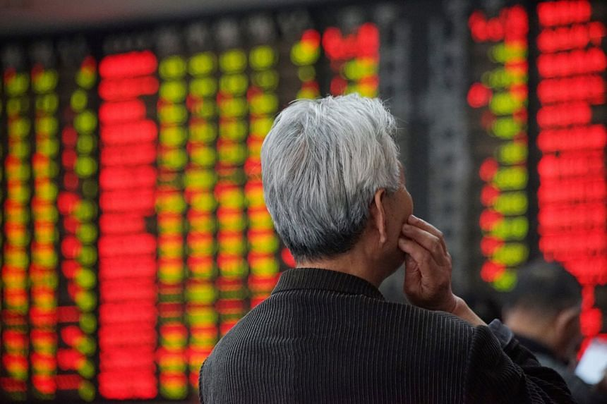 An investor looks at an electronic board showing stock information at a brokerage house in Nanjing, Jiangsu province, China, on April 16, 2018.