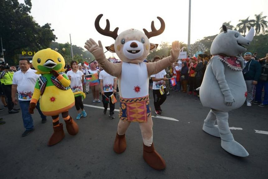 People dressed up as the mascots for the 2018 Asian Games take part in a parade to mark the 100-day countdown to the start of the games in Jakarta on May 13, 2018.