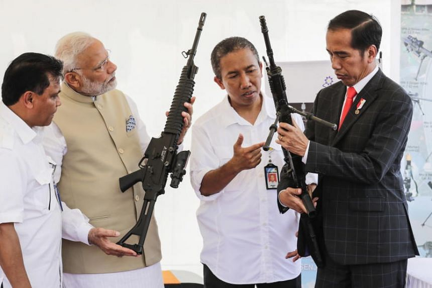 Indian Prime Minister Narendra Modi and Indonesian President Joko Widodo check rifles produced by PT Pindad during a visit to the National Monument in Jakarta on May 30, 2018.