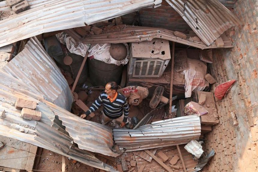 A resident clears debris from a house damaged by cross-border firing between India and Pakistan soldiers at Kanachak village near the India-Pakistan border, on Jan 22, 2018.