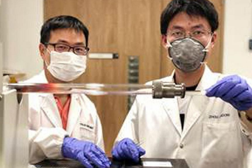 Assistant Professor Liu Zheng (left) and Dr Zhou Jiadong insert a ceramic boat, containing salt mixed with other components used to make transition-metal chalcogenides, into a furnace.