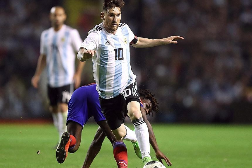 Captain Lionel Messi, who scored a hat-trick, evading a tackle by Haiti's Bryan Alceus in Argentina's 4-0 friendly win at home. Coach Jorge Sampaoli was pleased with contributions from substitutes Cristian Pavon and Sergio Aguero.