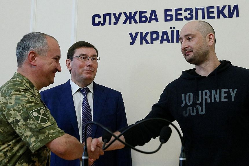Mr Arkady Babchenko (right), who was reported to have been shot dead in his flat in Kiev, at a news briefing yesterday with Ukrainian Prosecutor General Yuriy Lutsenko (centre) and state security service head Vasily Gritsak.