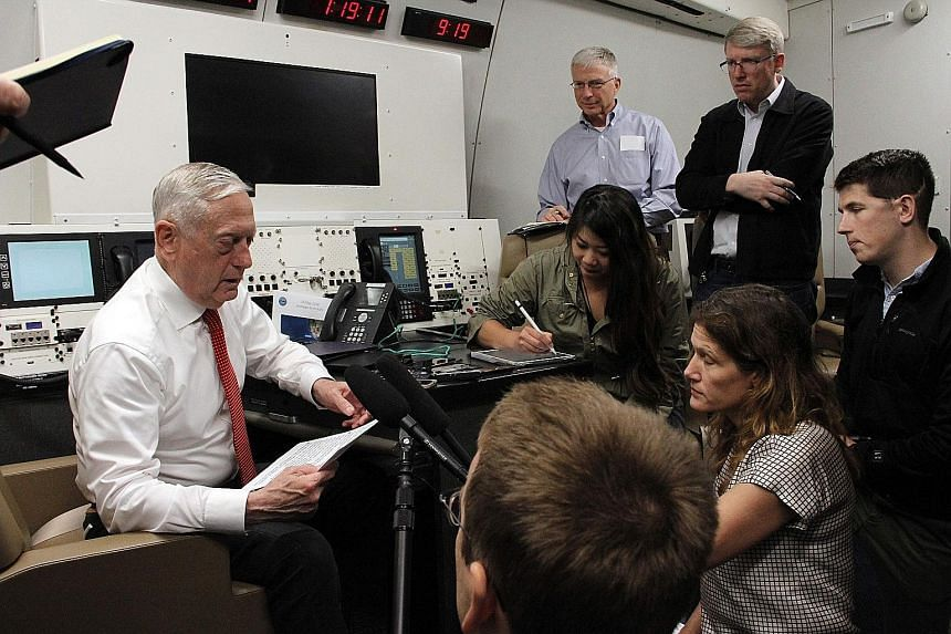 US Defence Secretary James Mattis with reporters aboard a US military plane yesterday as he flew to Hawaii. He vowed the US would continue confronting China over its territorial claims in the South China Sea.