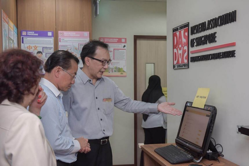 Member of Parliament for Marine Parade GRC Seah Kian Peng is given a tour at the opening of the Dyslexia Association of Singapore Serangoon Learning Centre.